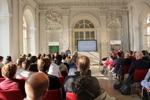 Der Tagungssaal in der Orangerie. Publikum von hinten, vorne Plakate, großer Bildschirm und Referierender
